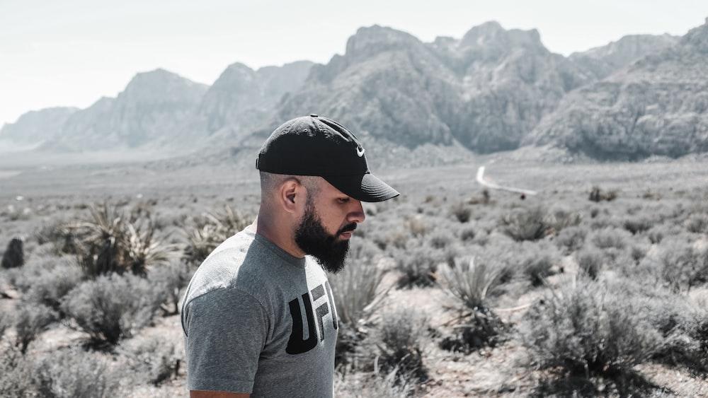 man standing beside grass near mountain