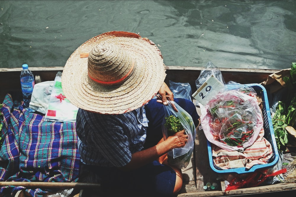person wearing straw hat holding clear plastic pack