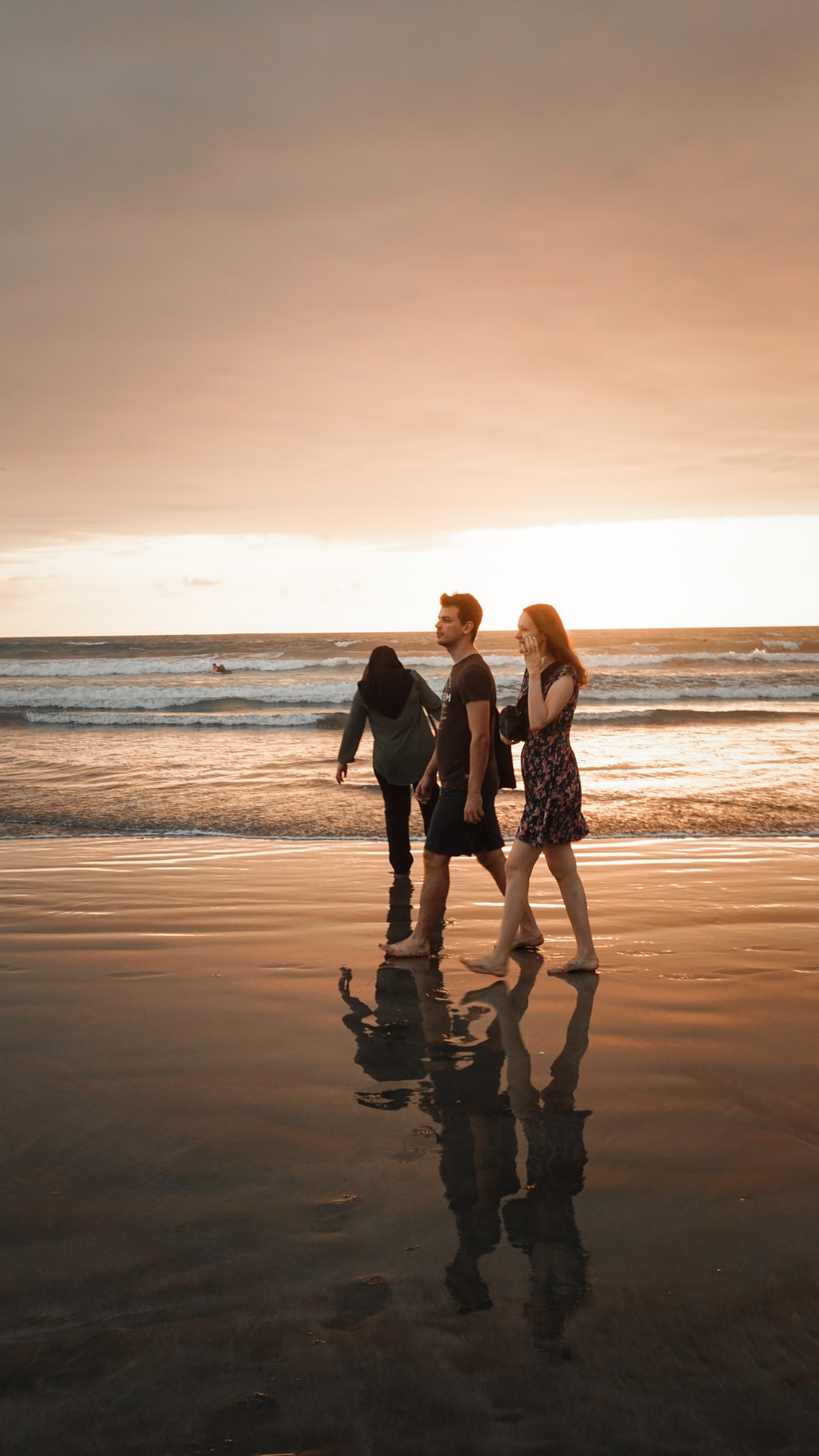 two women and man walking on seashore