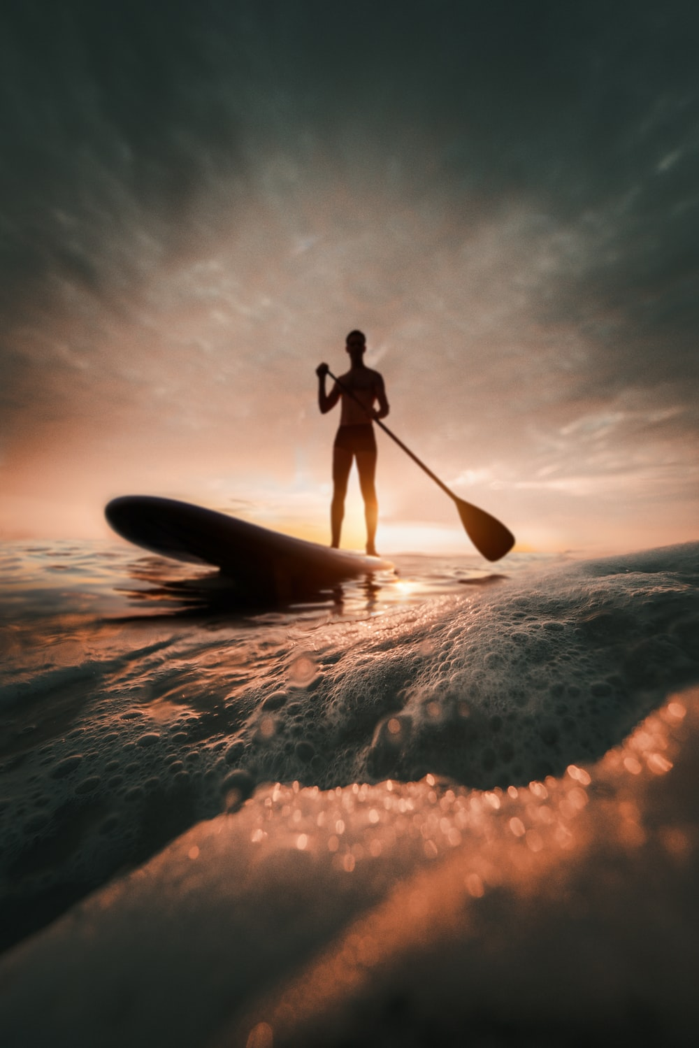 person paddle boarding during golden hour