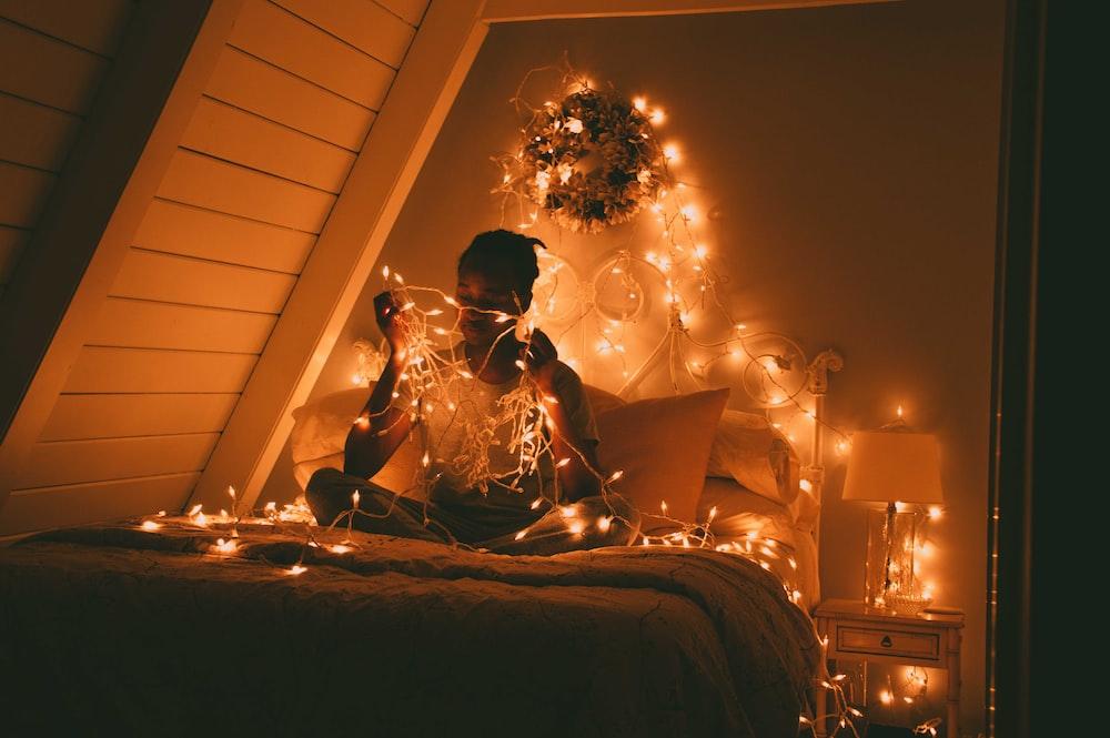 man sitting on bed holding light stripes