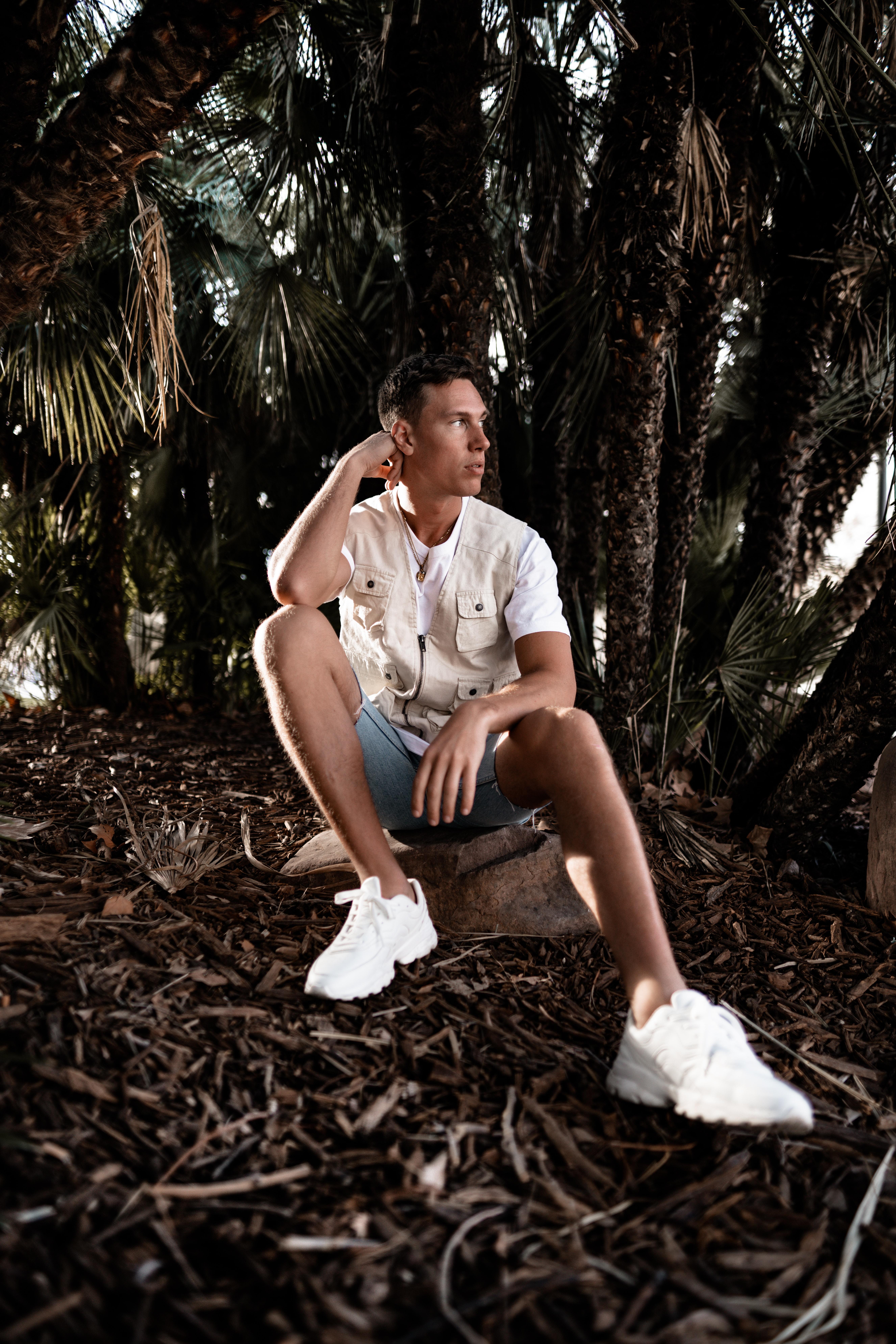 man sitting on rock beside palm trees