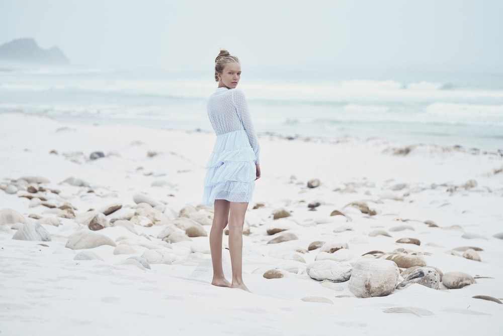 woman standing by the sea shore during daytime