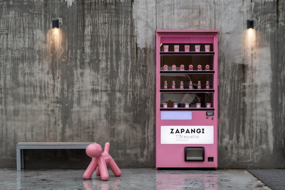pink toy beside pink Zapangi vending machine