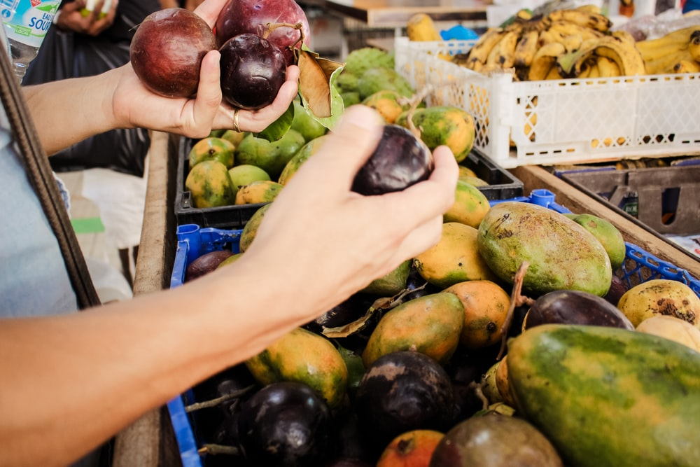 person picking fruits from stall