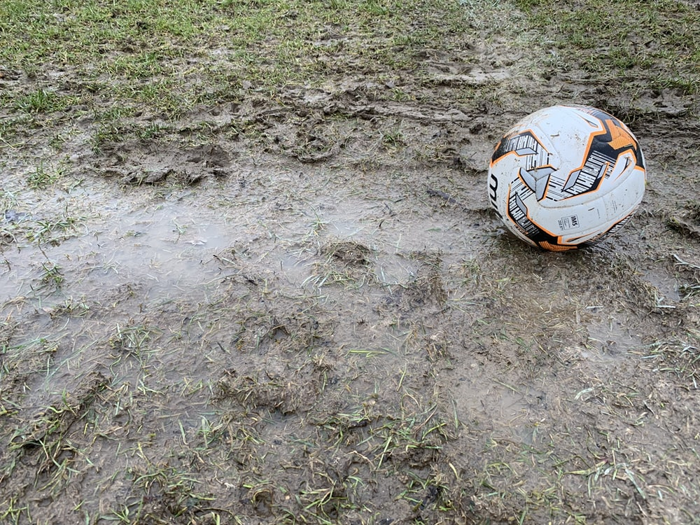 white and orange soccer ball on the ground