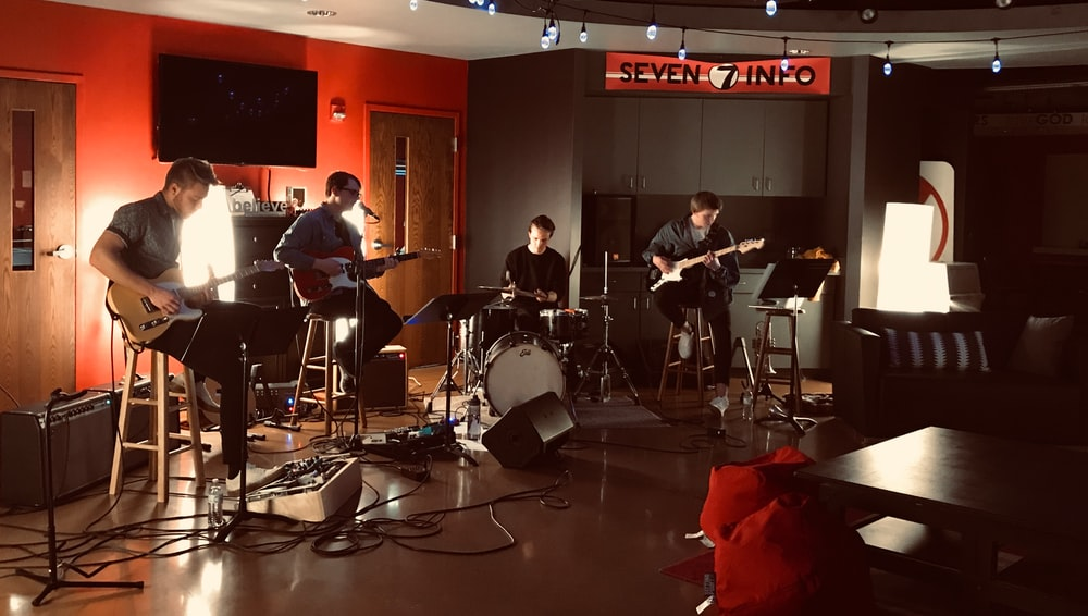 four boy band performing on Seven Info room