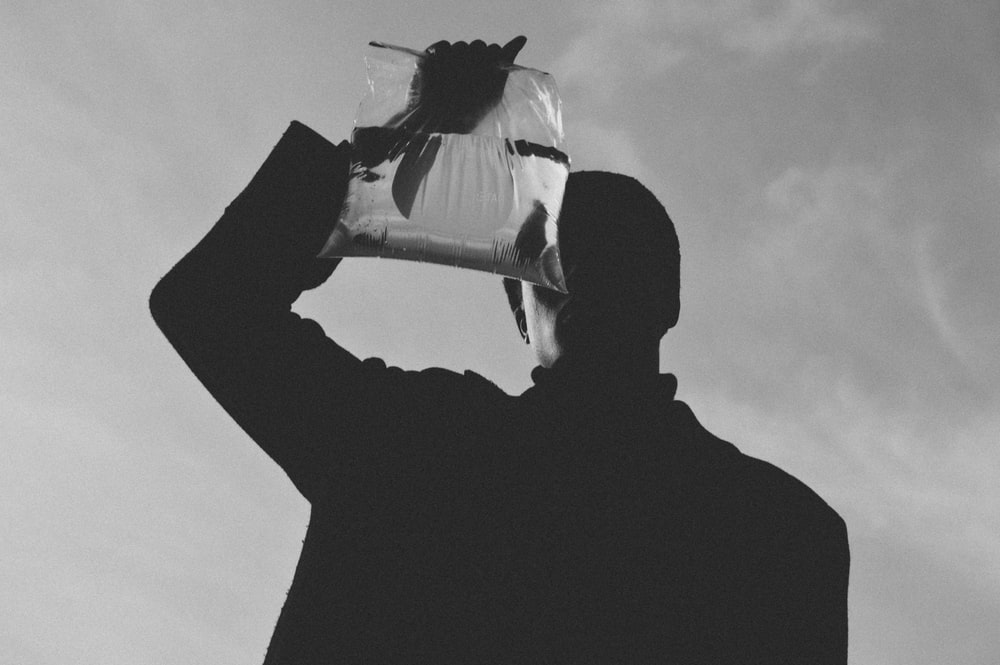 grayscale photo of person holding plastic with water and fish
