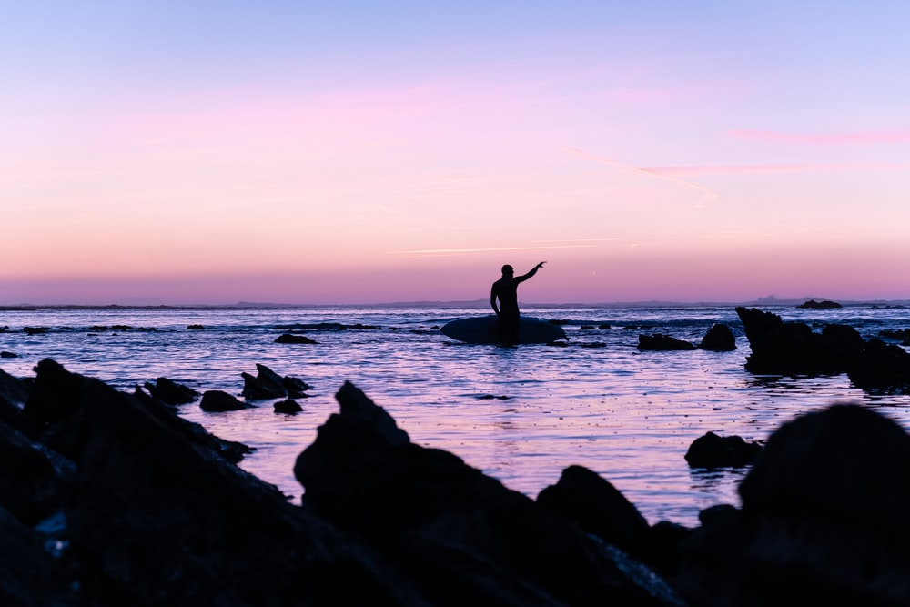 silhouette of person standing on rock beside beach