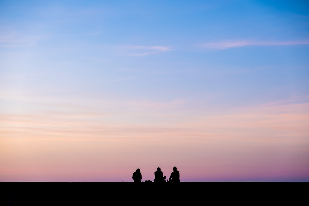 silhouette photography of three person sitting under sky