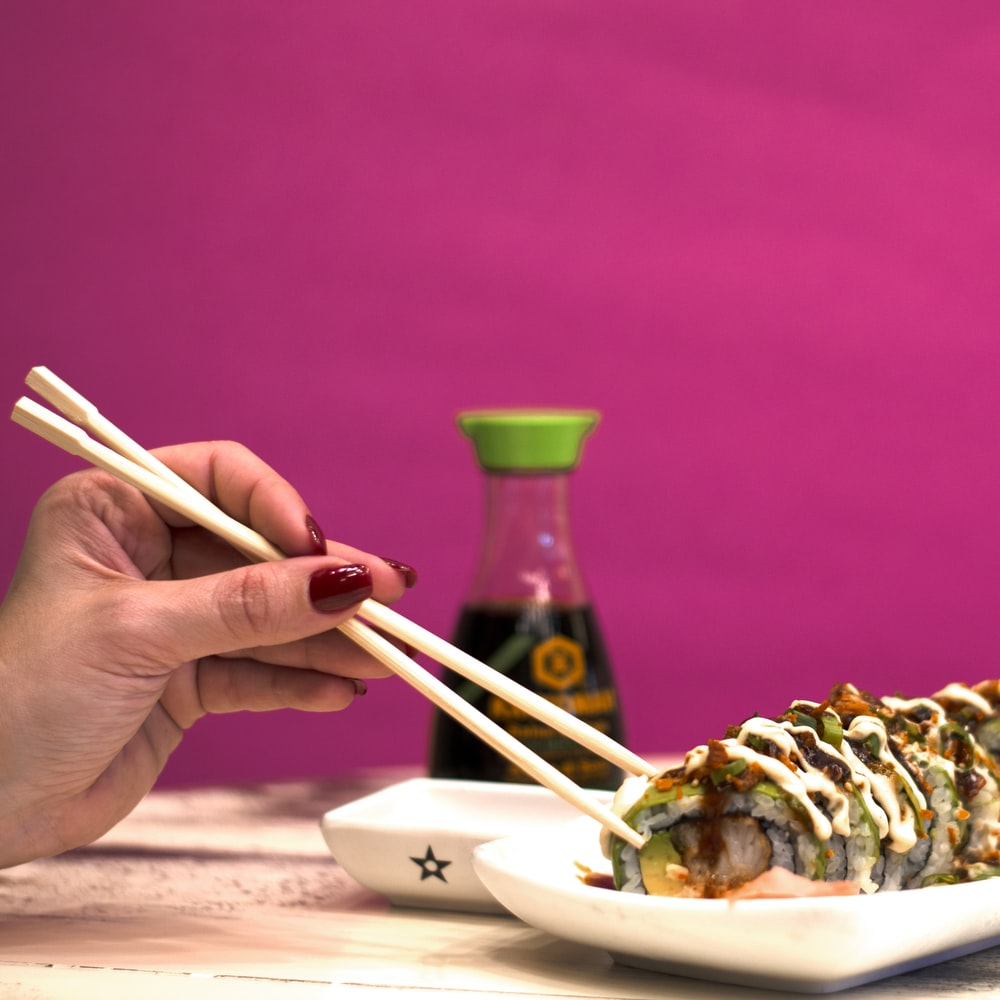 person using chopstick on cooked food