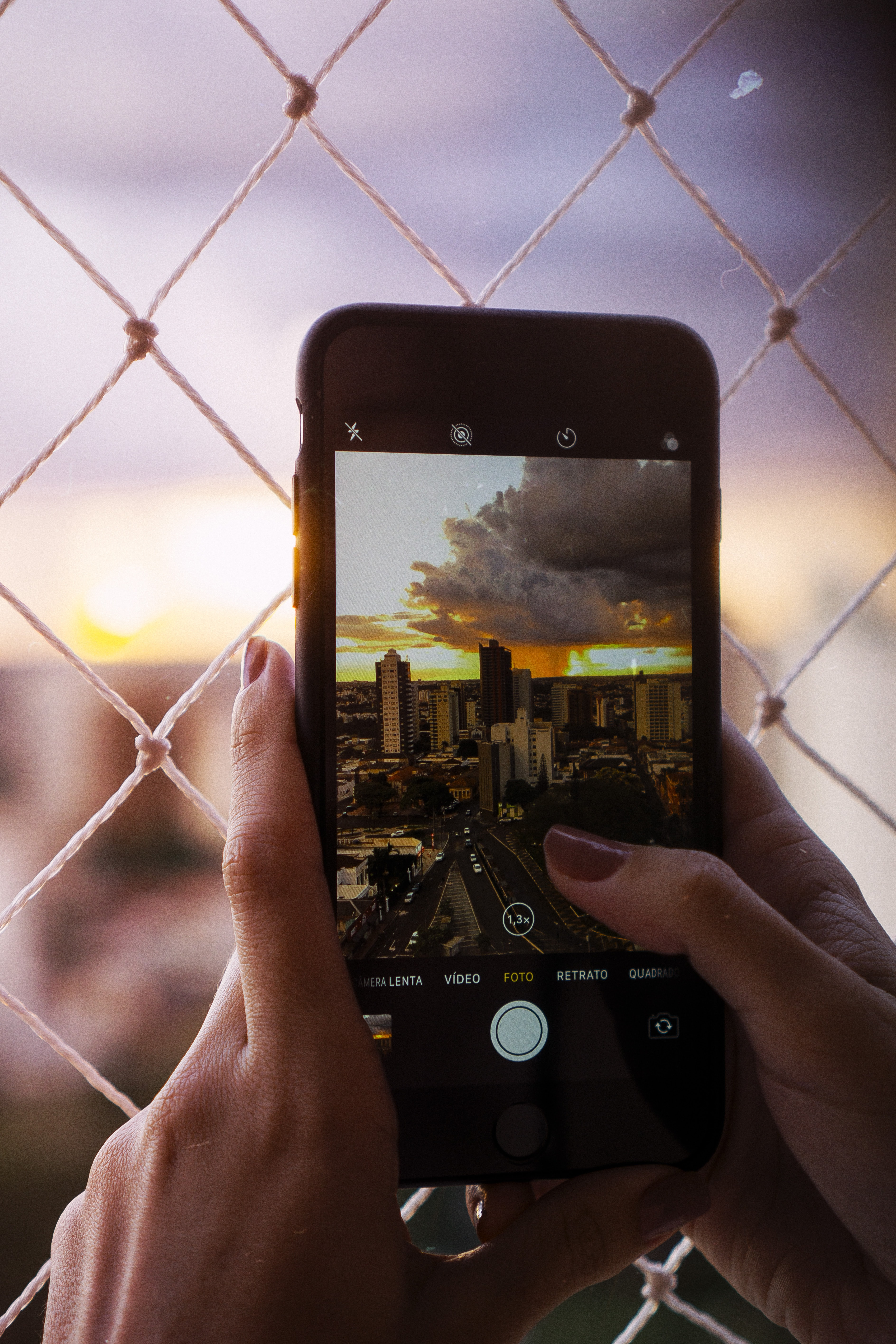 person holding smartphone capturing city in closed-up photography