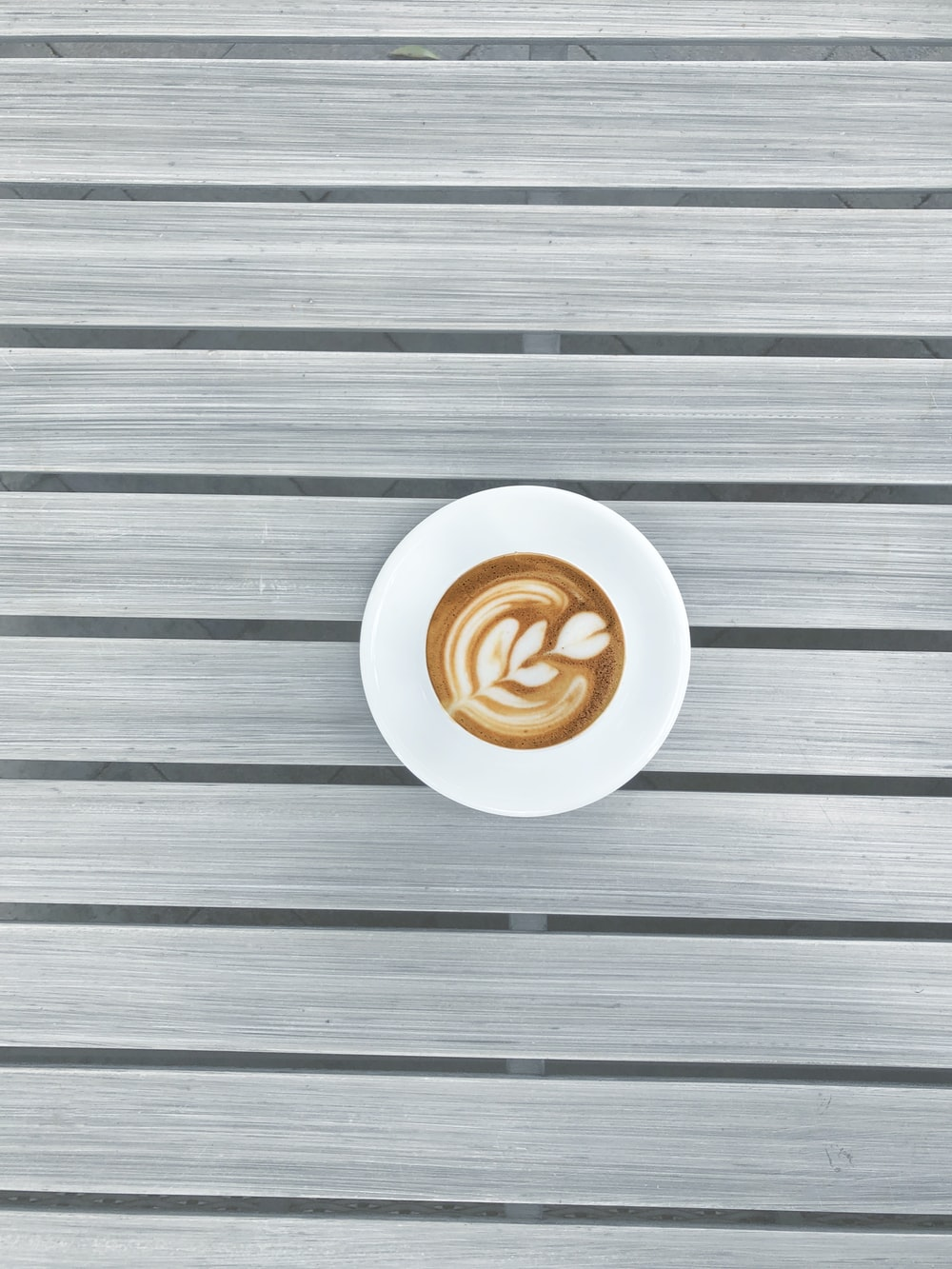 round white espresso coffee on grey striped surface