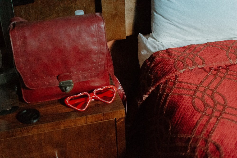 red leather bag on brown nightstand