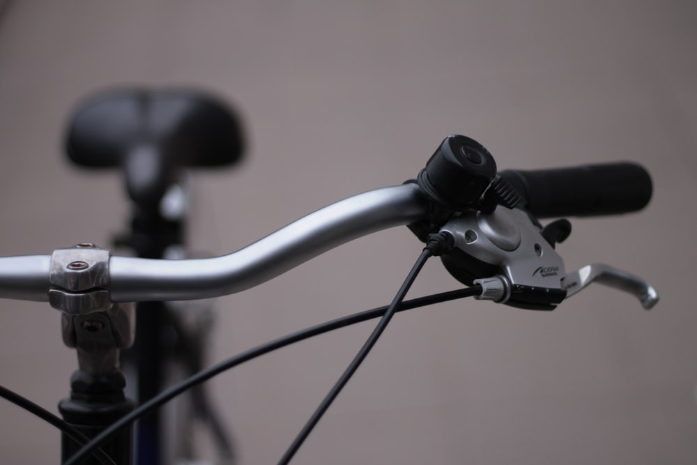 selective-focus photograph of silver bike handlebar