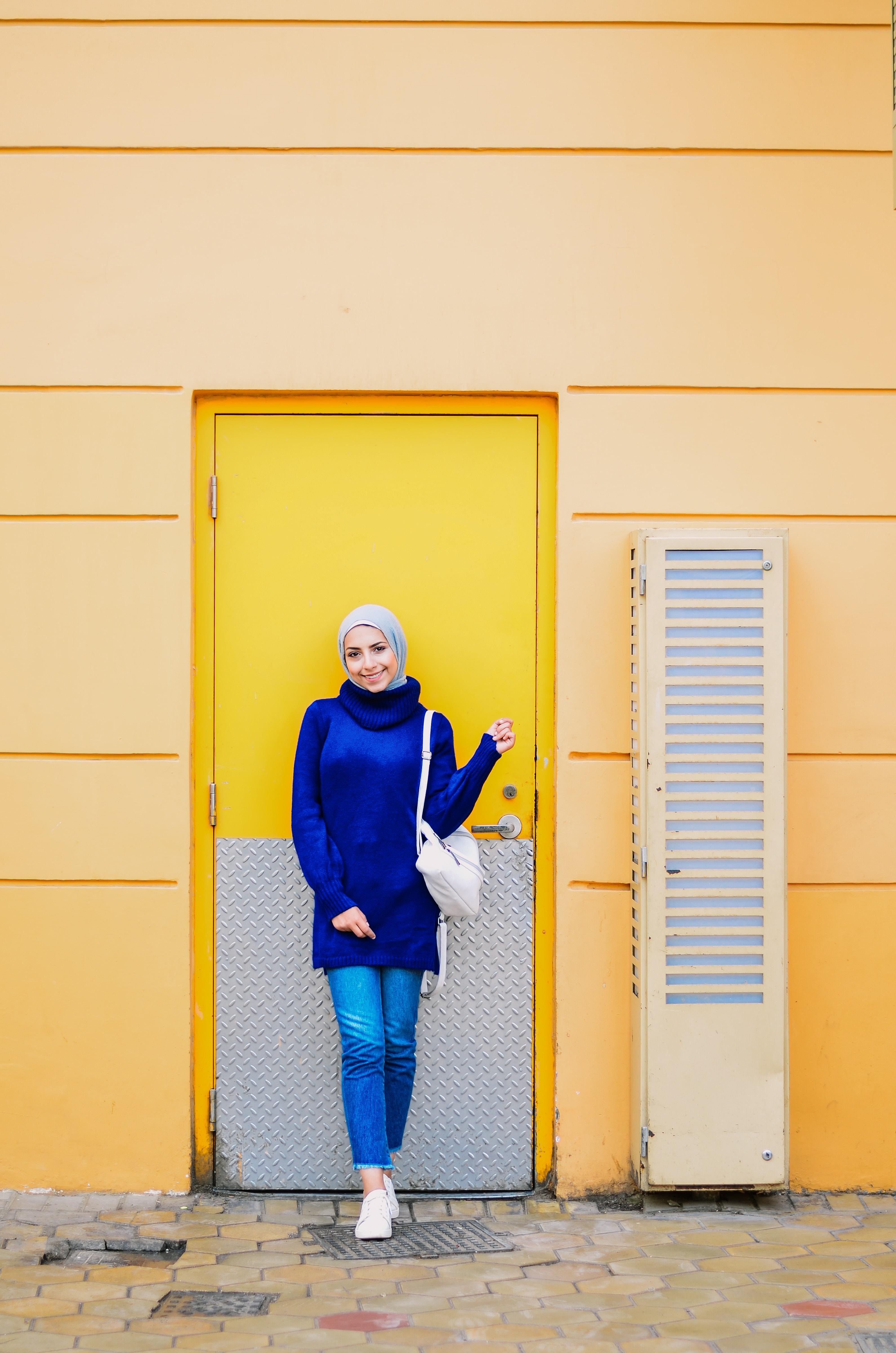 woman standing in front of yellow door