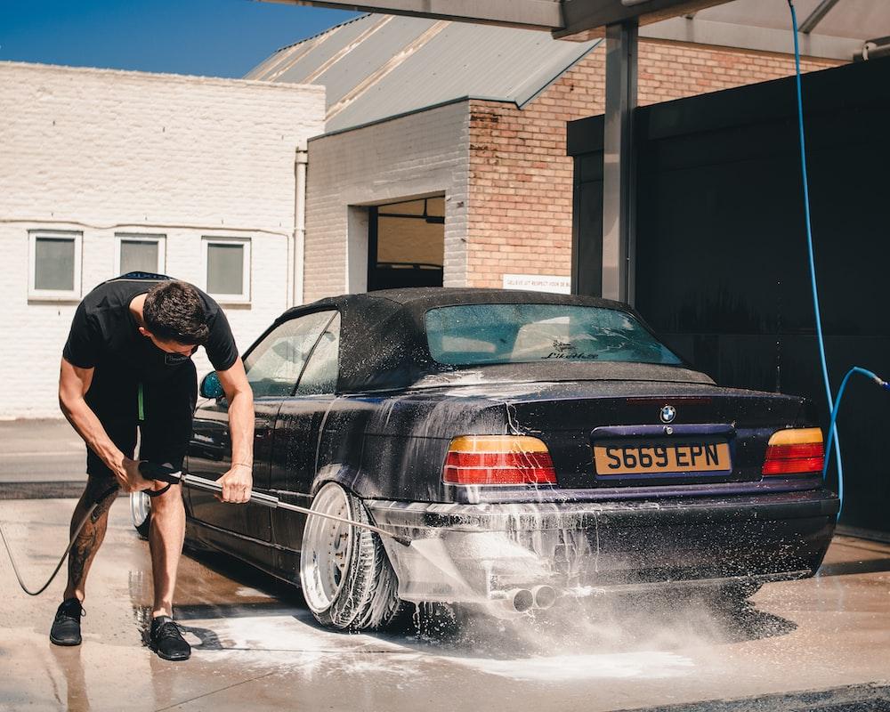 man washing BMW coupe