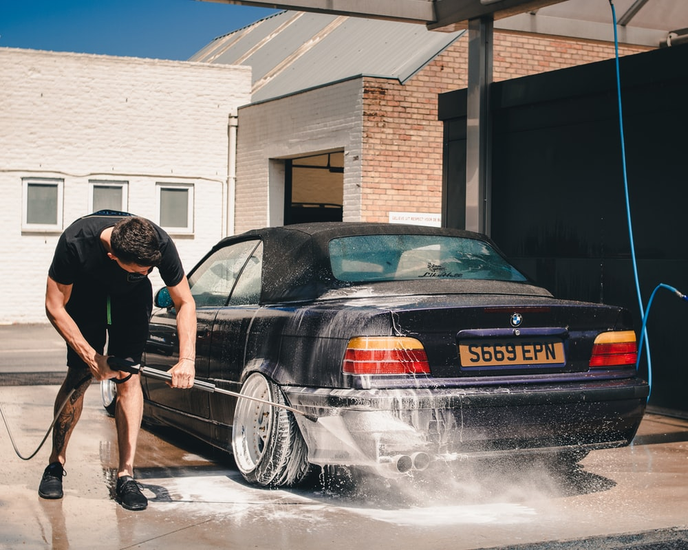 man washing BMW coupe