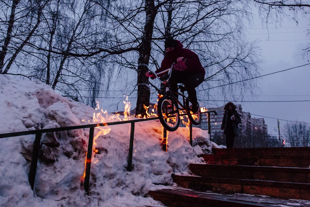 man doing bicycle tricks on hand rail during winter