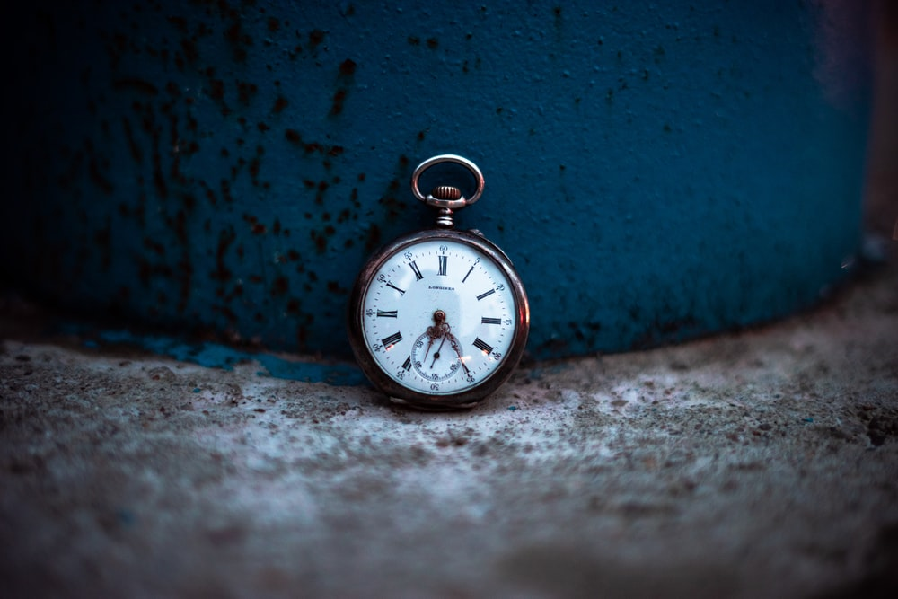 shallow focus photo of silver-colored pocket watch