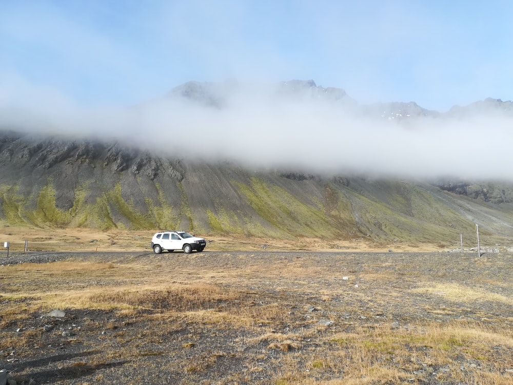 white SUV running on soil over clouds