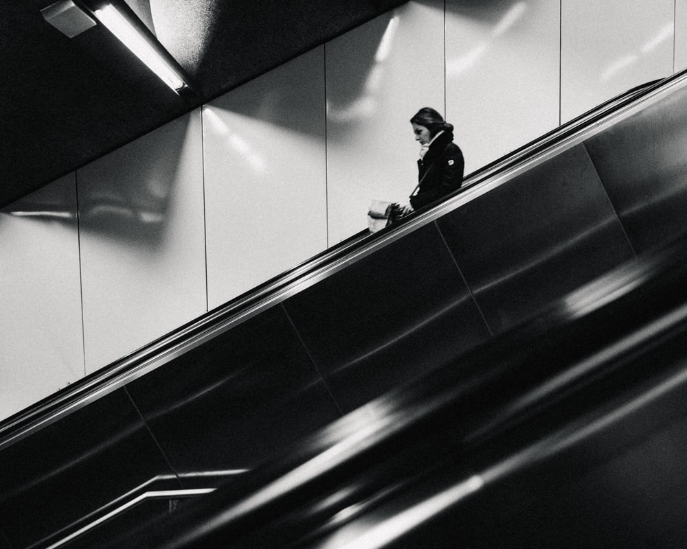 grayscale photography of woman using escalator going down