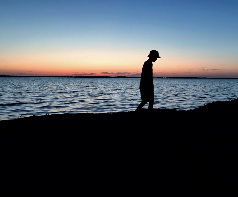silhouette of person walking near body of water