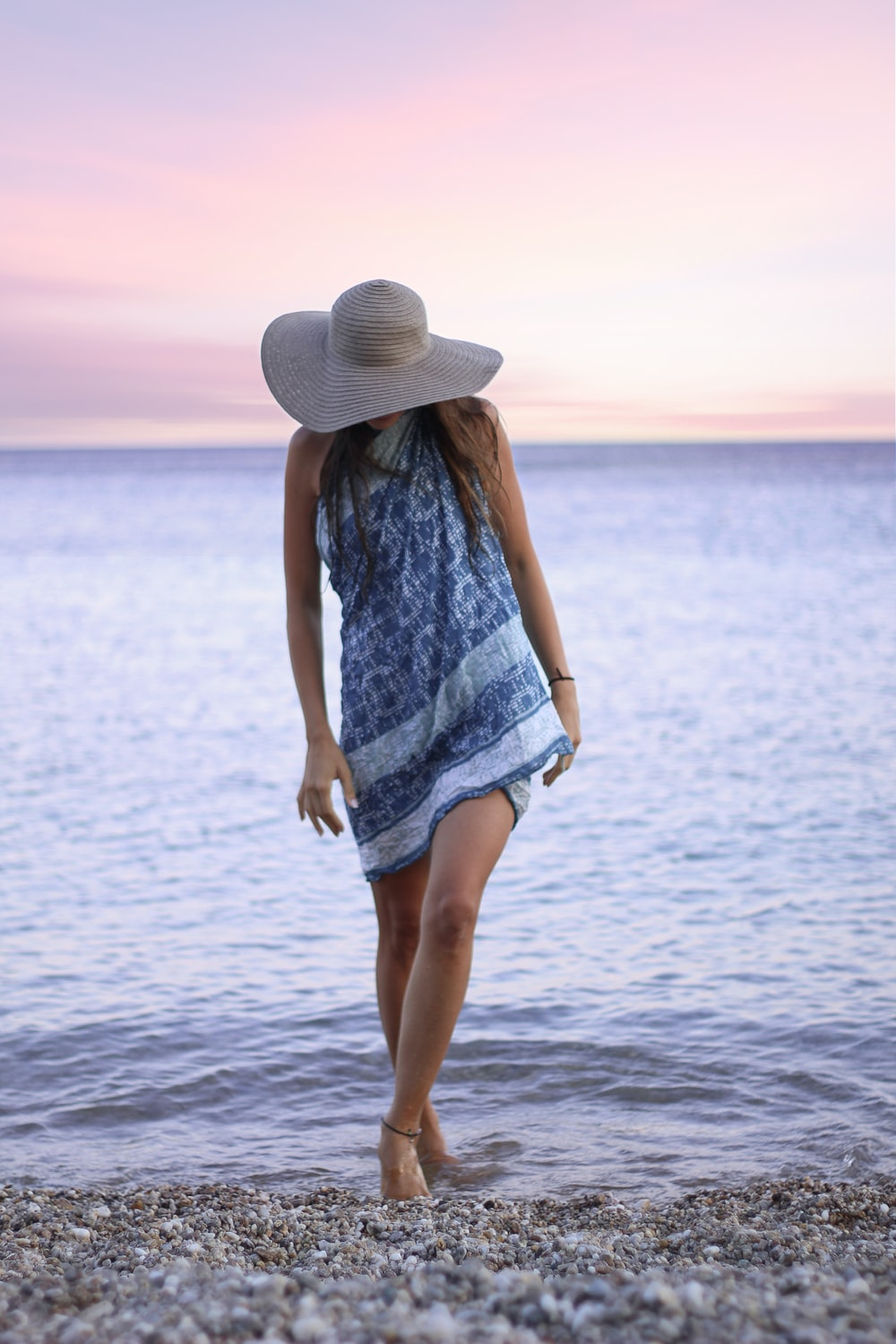 woman in blue and white dress wearing sunny hat