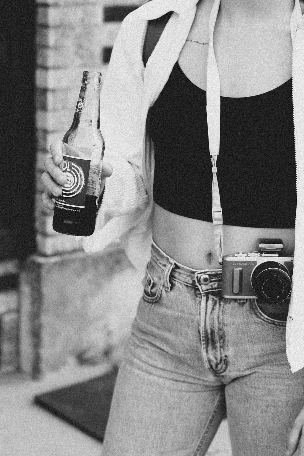 grayscale photography of woman holding product bottle