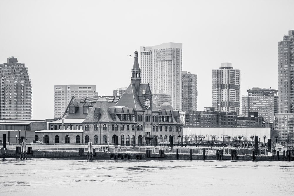 panoramic grayscale photo of building facing body of water