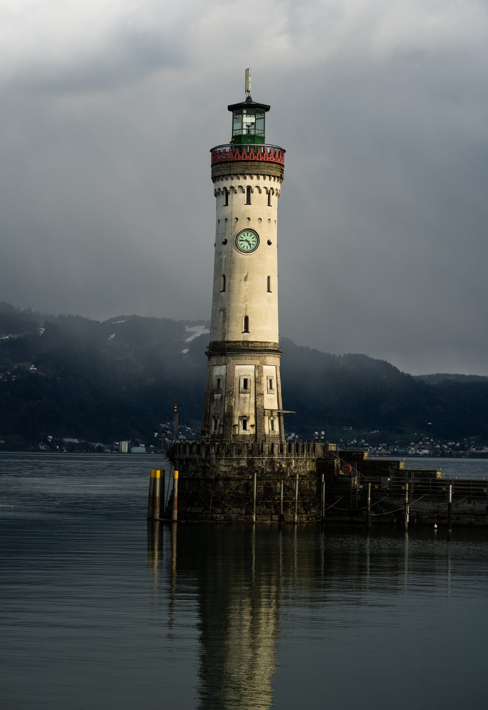white lighthouse near calm body of water