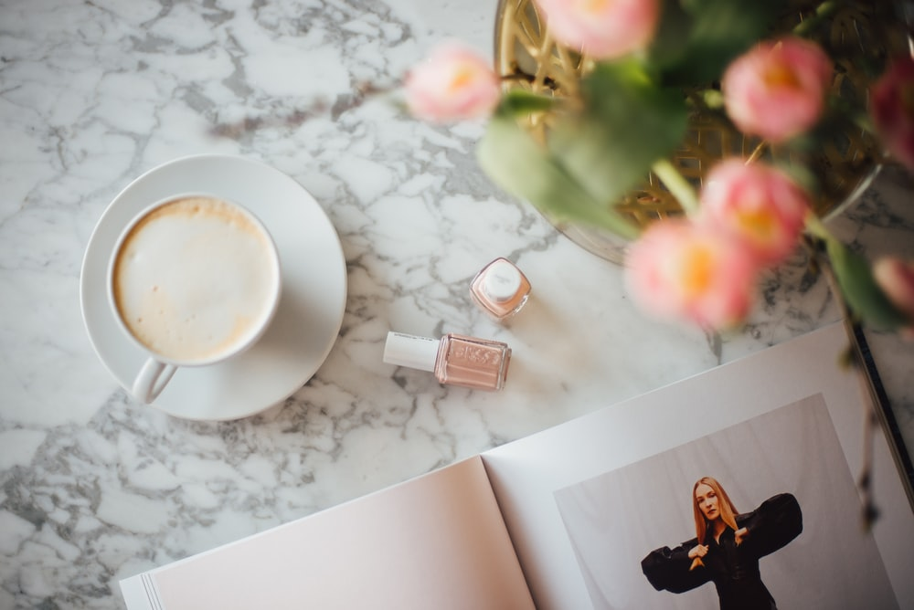 coffee on cup with saucer beside nail polish bottles, book, and flowers