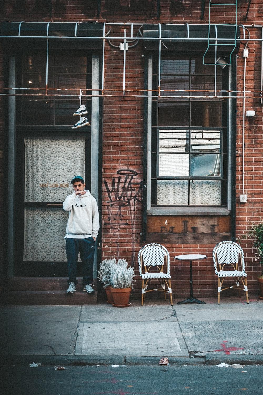 woman in white hoodie standing near brown building