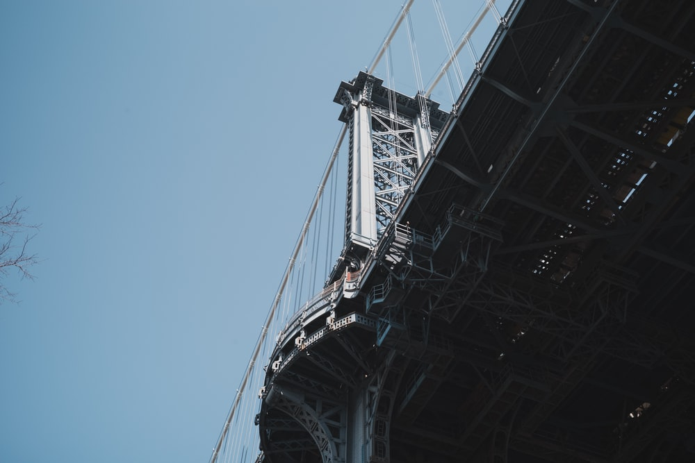 low-angle photo of bridge under blue sky