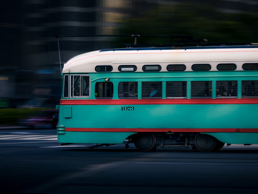 teal and white train running on road