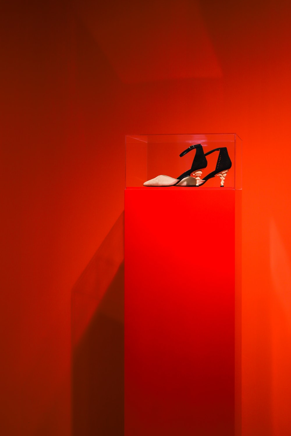 black-and-brown ankle-strap heeled sandals on red and clear glass display counter