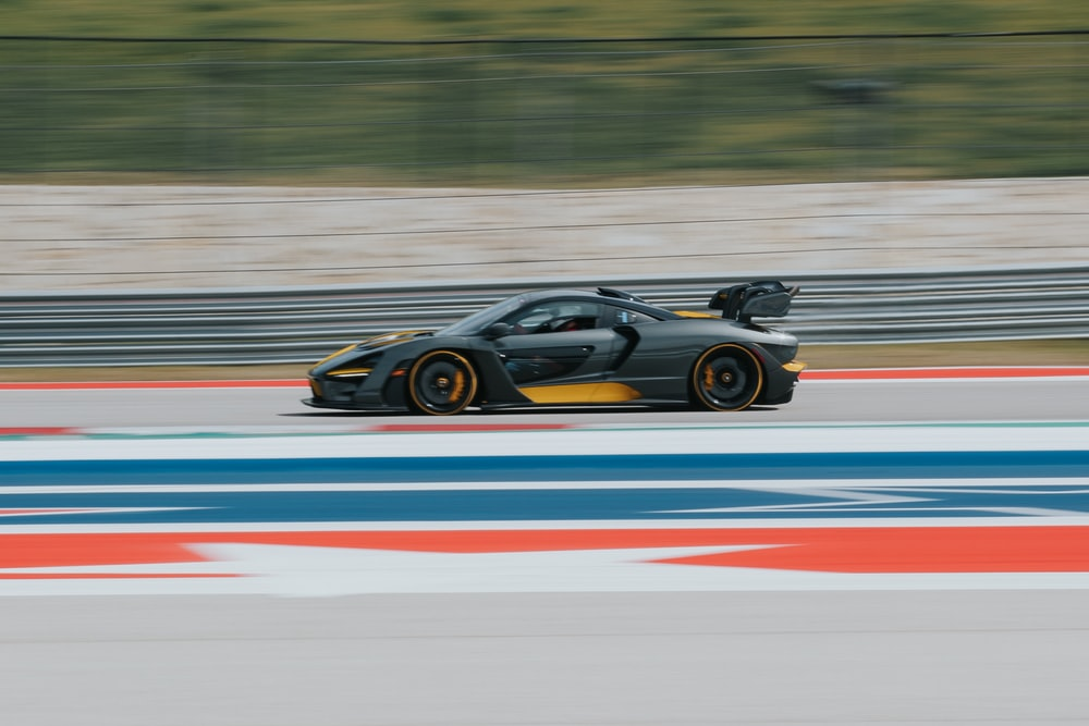 black and yellow sports car speeding on track
