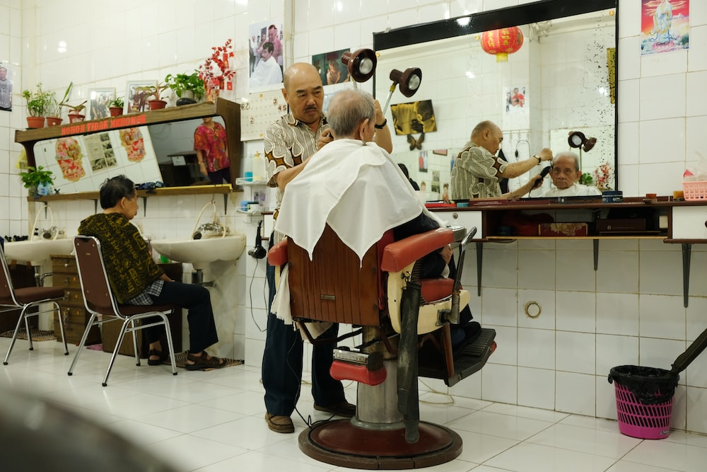 woman cutting the hair of man sitting on barber armchair