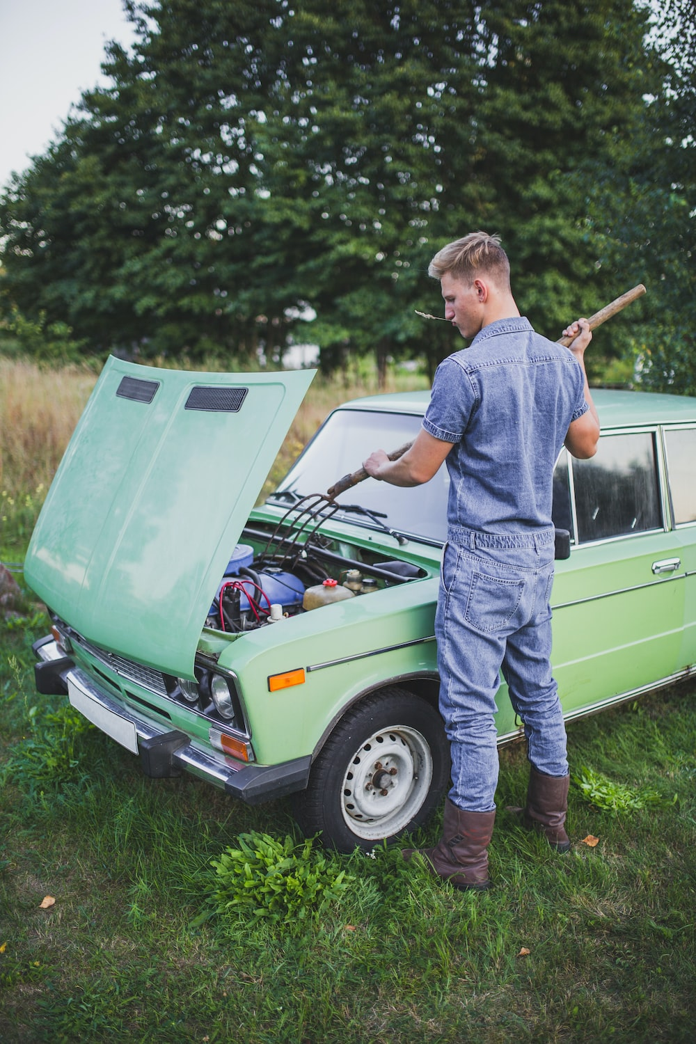 man in blue top fixing green car during daytime