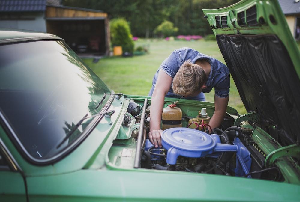 man checking vehicle engine