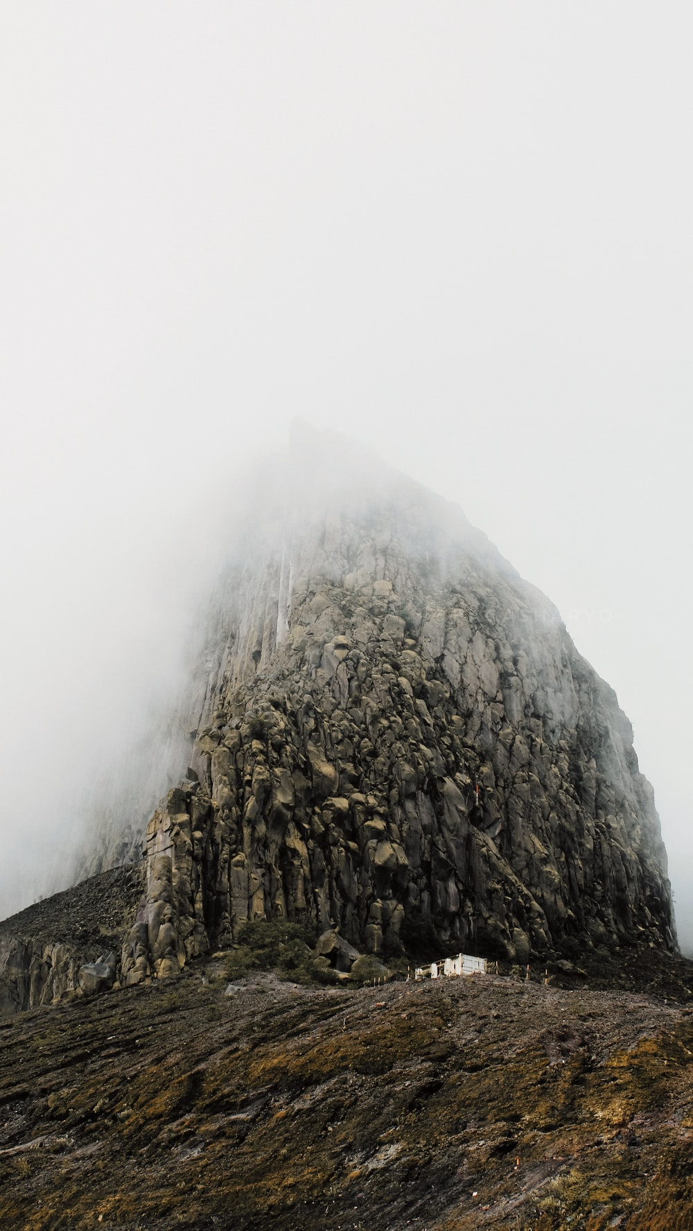 gray rock formation under white skies