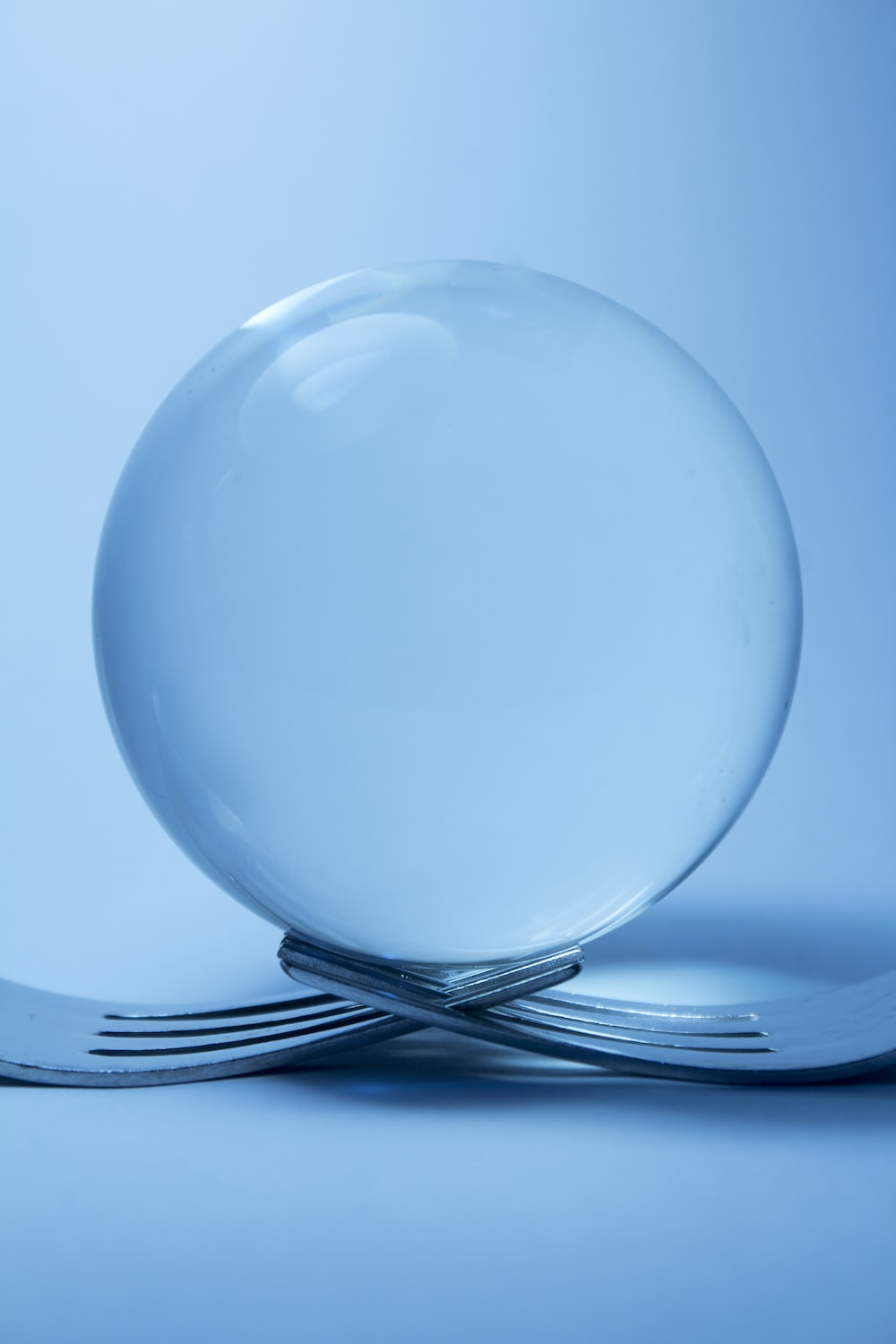 clear glass ball on top of two forks