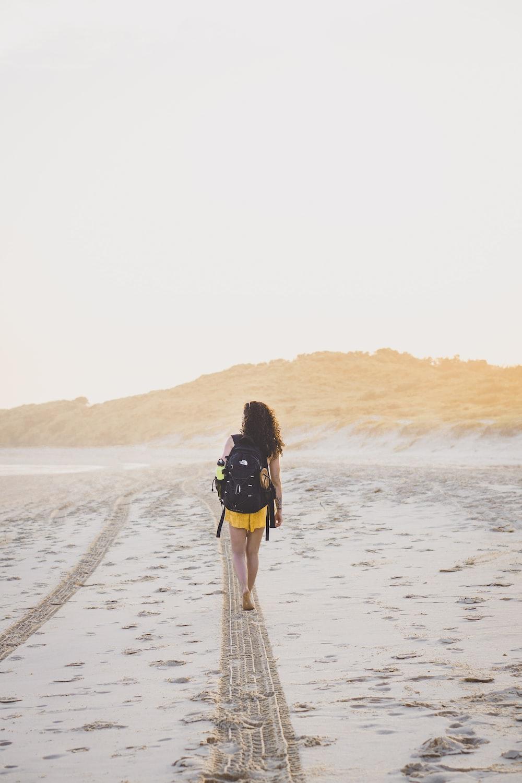 woman wearing yellow bottoms walking on sand during daytime