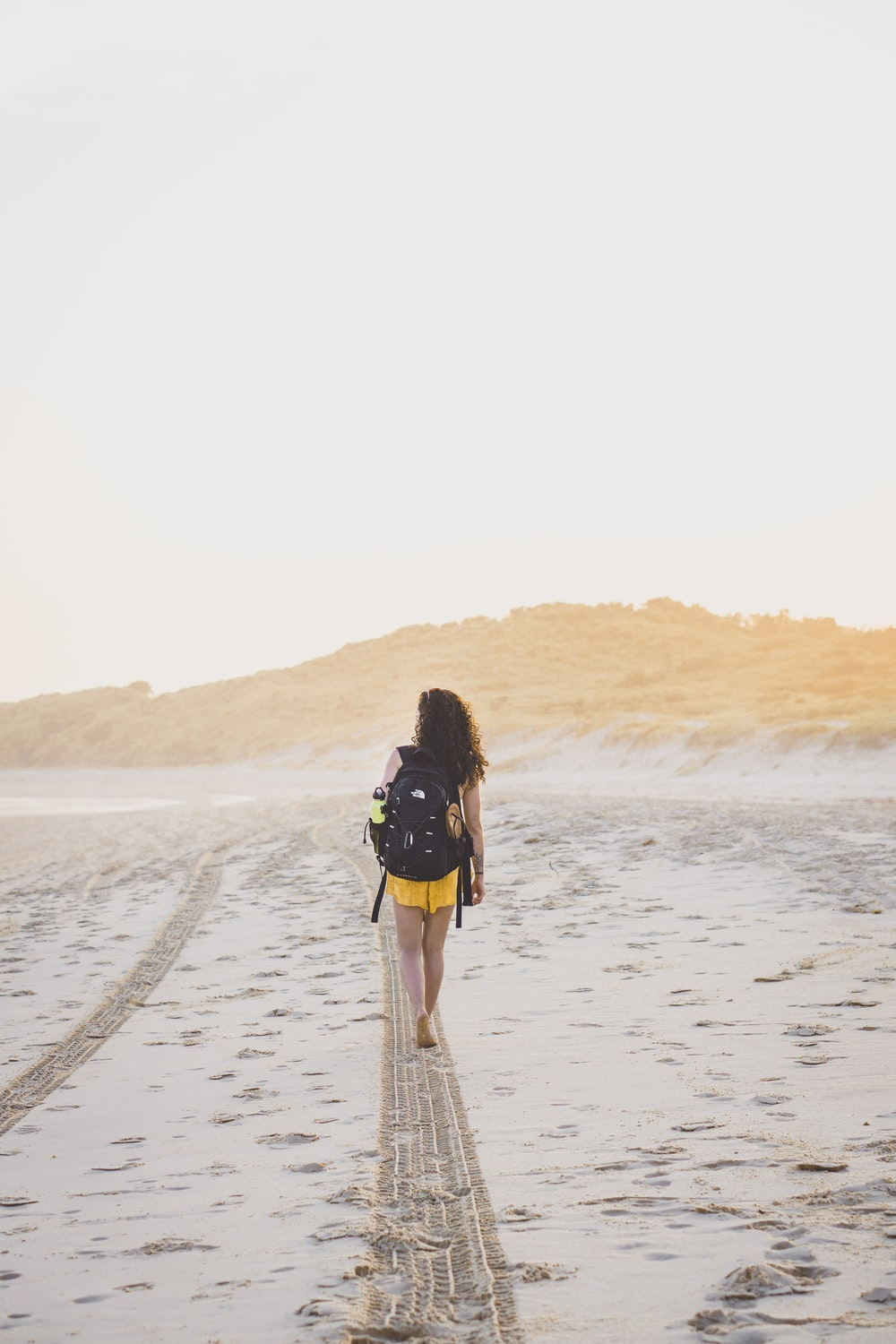 woman wearing yellow bottoms walking on sand during daytime
