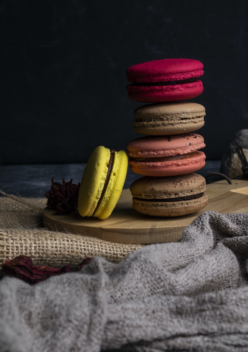 five yellow, red, pink, and brown French macaroons on coaster