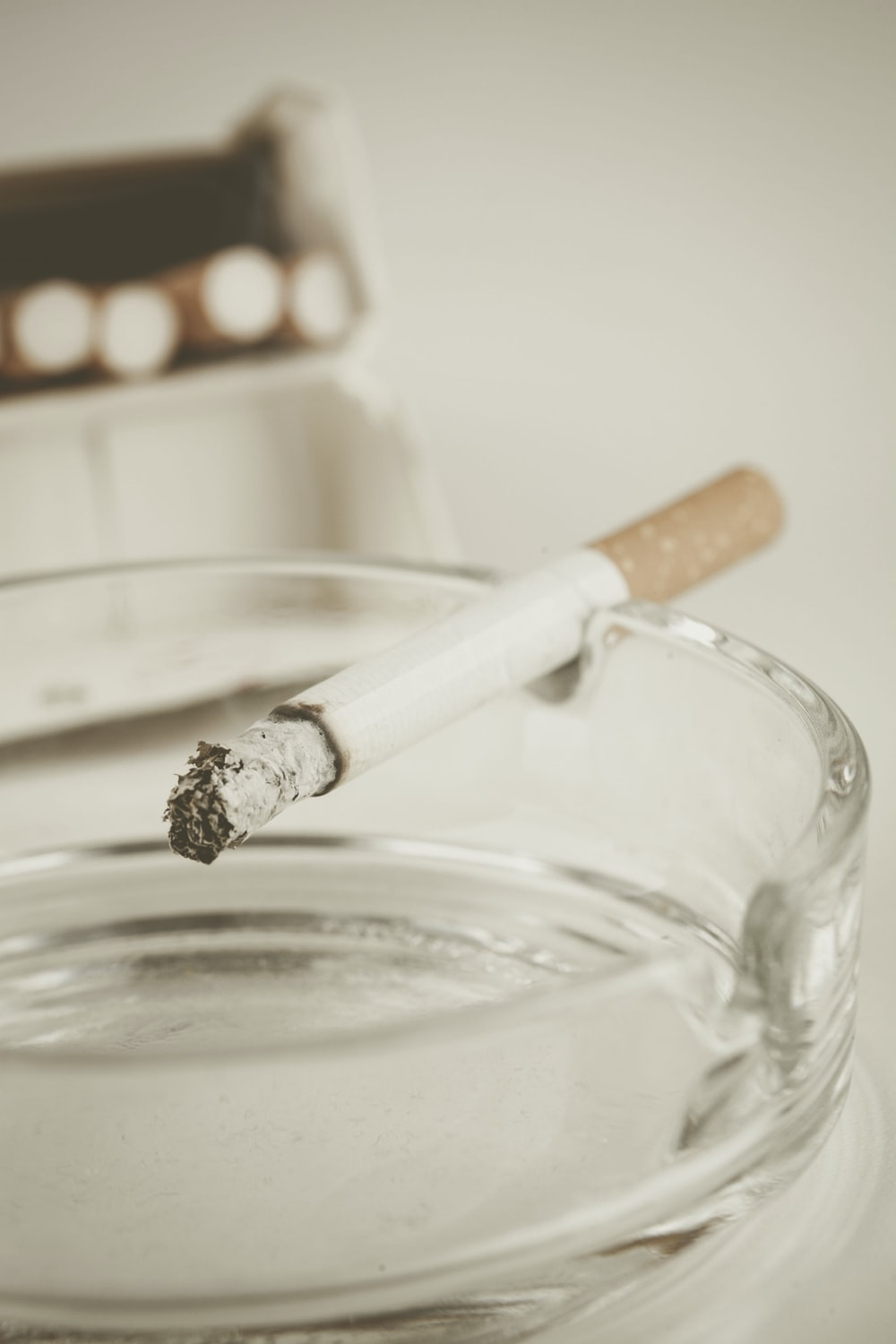 lighted cigarette stick on glass ashtray