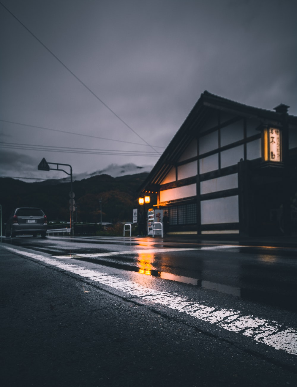 yellow lighted house near wet road