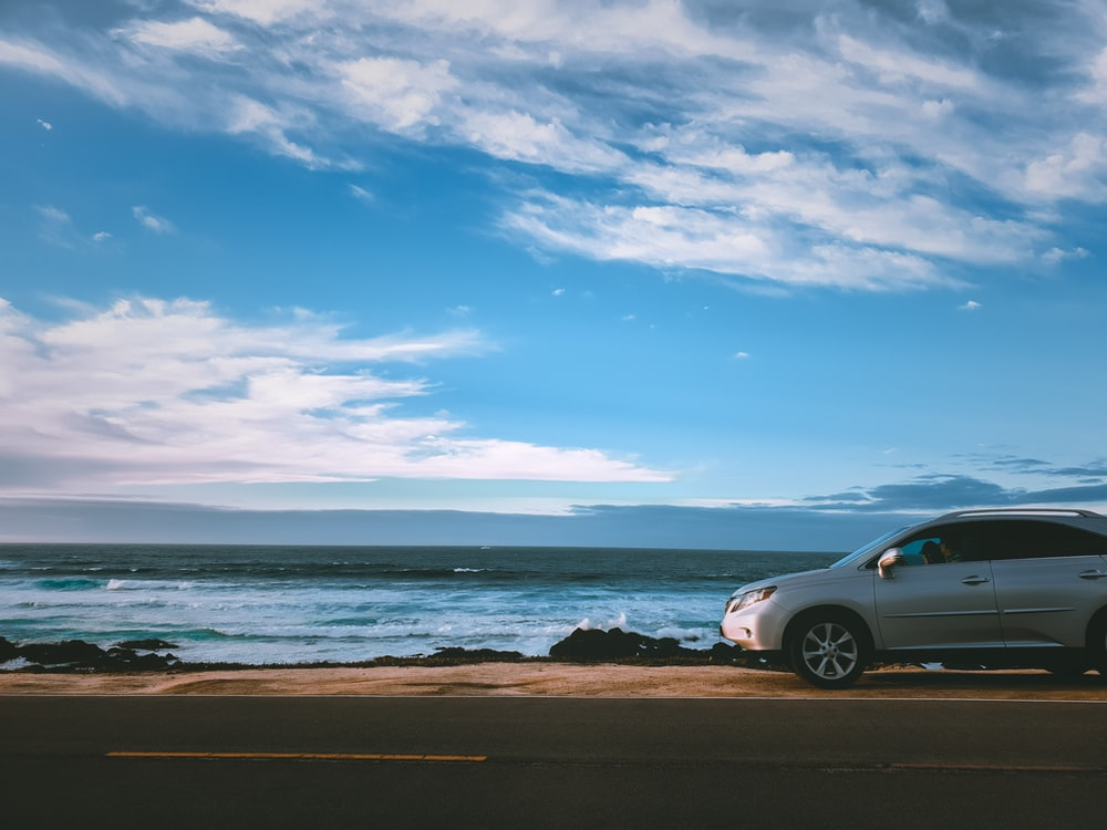 silver vehicle parked beside body of water