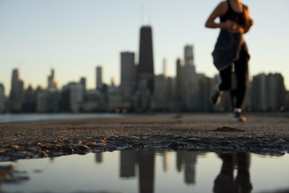woman running near body of water