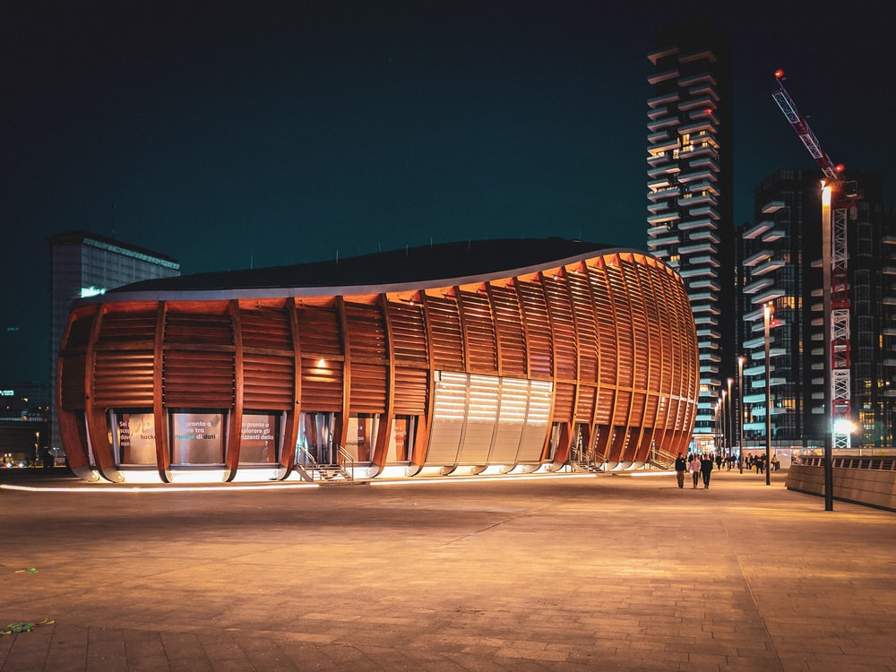 brown wooden framed building near building at nighttime